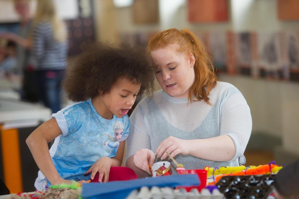 Woman helping child take part in arts and crafts.