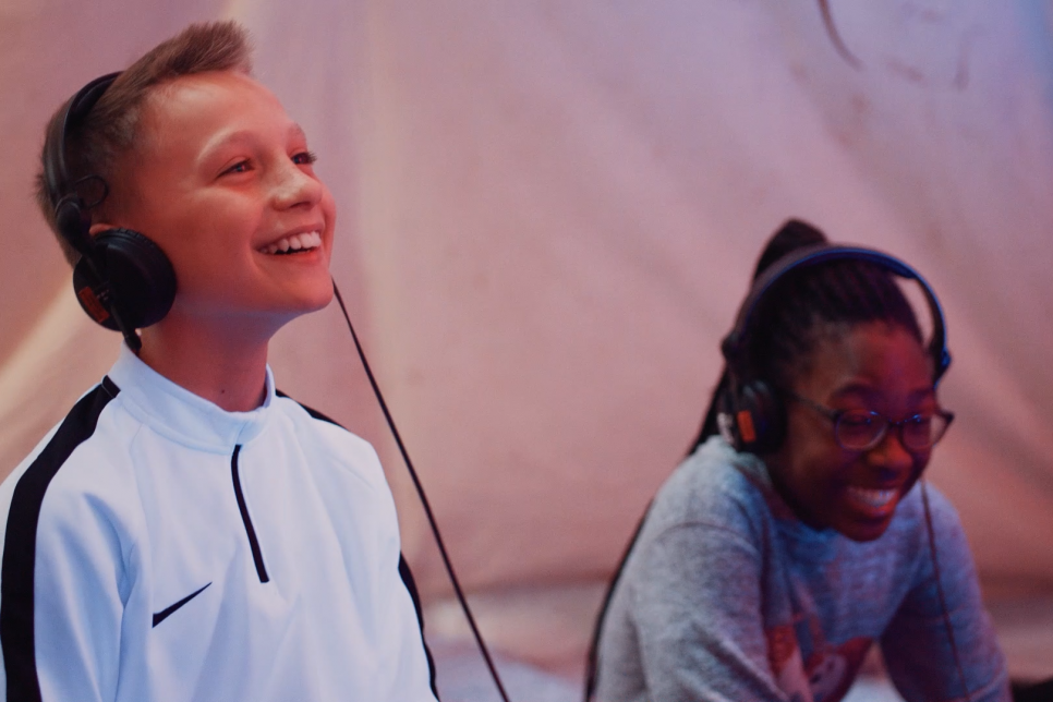Two children wearing headphones and laughing